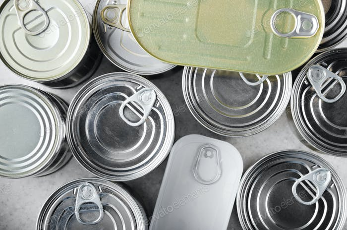 Flat lay view at various canned foods in tin cans on kitchen table