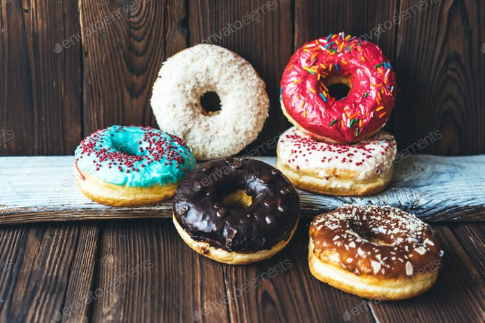 Assorted glazed appetizing donuts on a dark wooden background.