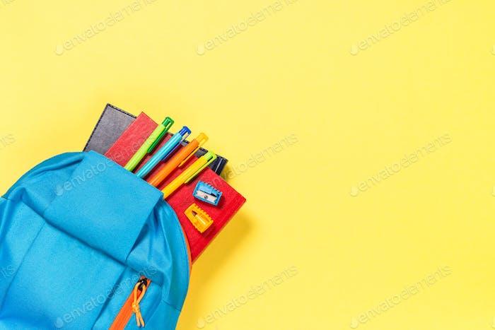 Schulrucksack mit Briefpapier auf gelbem Hintergrund