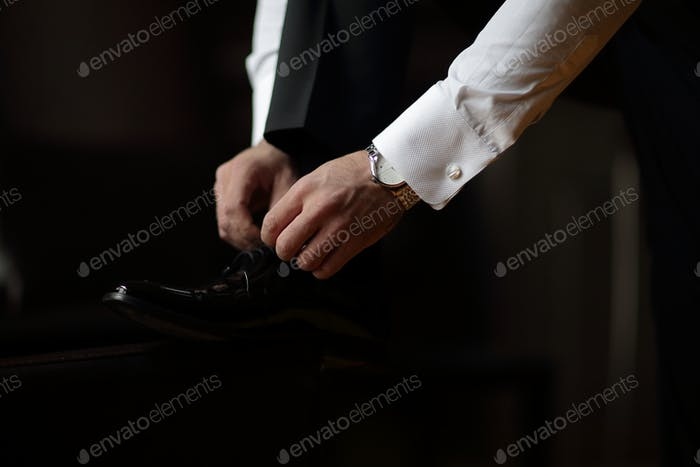 The groom ties his shoes