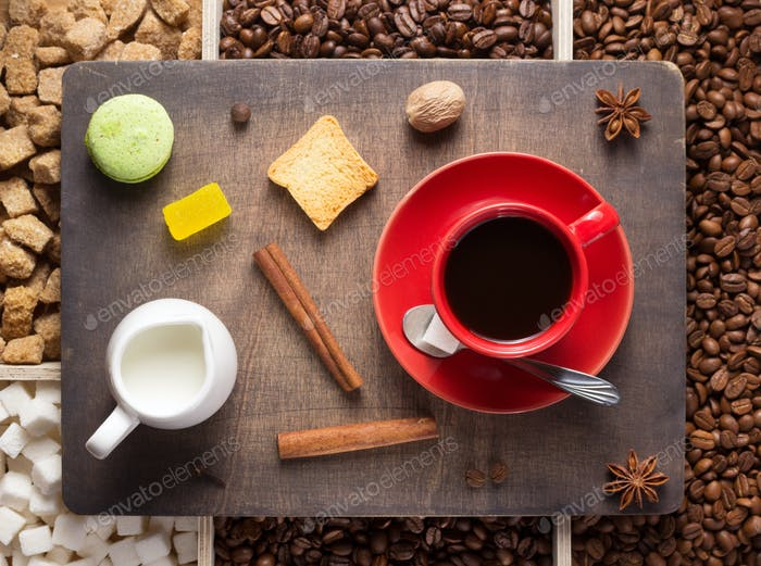 cup of coffee and beans on wooden tray
