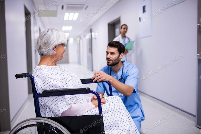 Männlicher Arzt interagiert mit älteren Patienten auf Rollstuhl