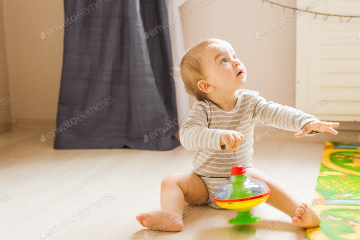 Cute child boy toddler playing with toy indoors