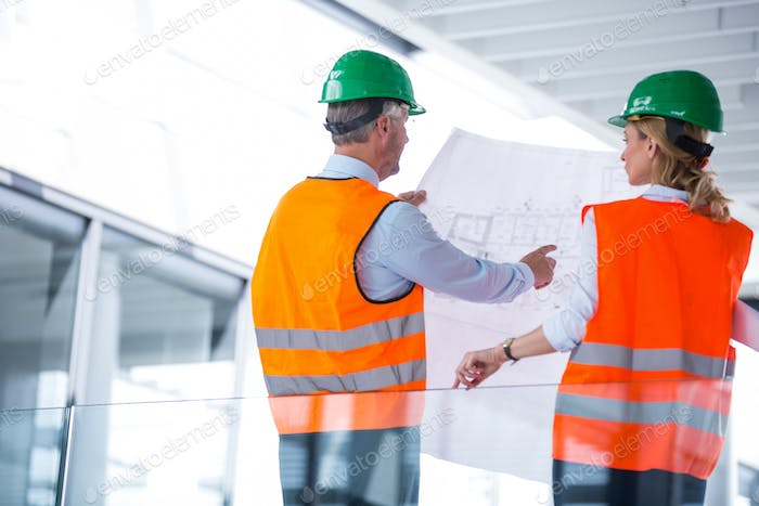 Architects discussing with blueprint in office corridor