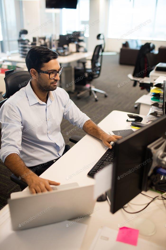 Businessman using laptop and desktop pc together