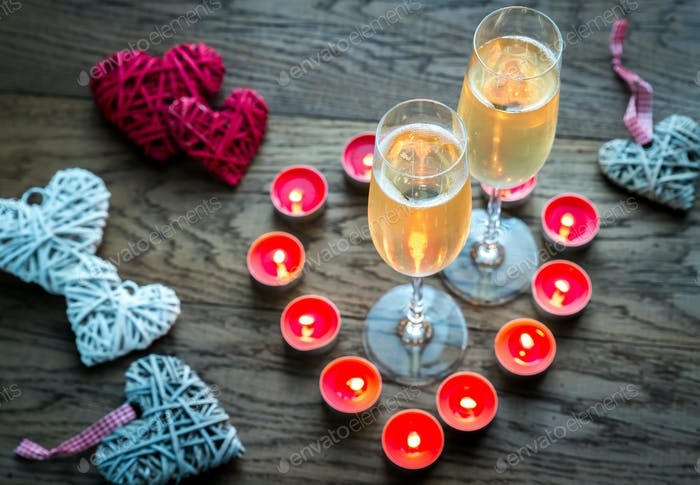 Two glasses of champagne inside of burning candles