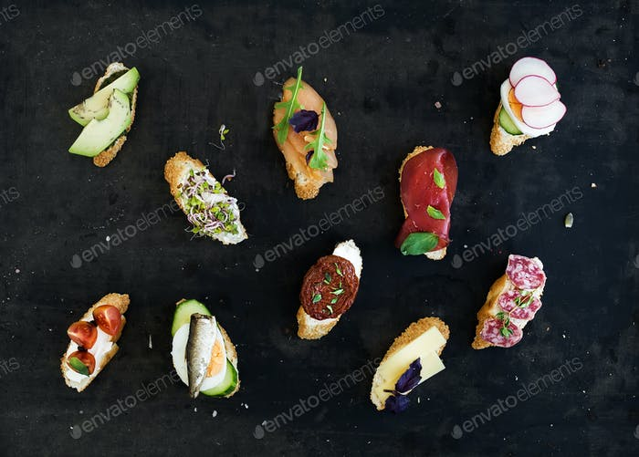 Mini sandwich set. Variety of small sandwiches on black backdrop