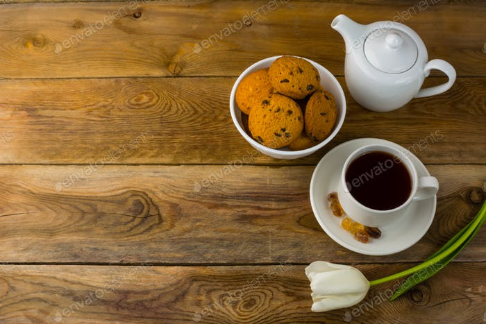 Tea cup, cookies  and teapot on wooden background, copy space