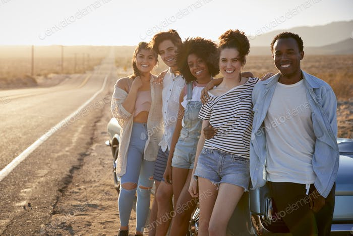 Portrait Of Five Friends Standing By Convertible Classic Car On Road Trip