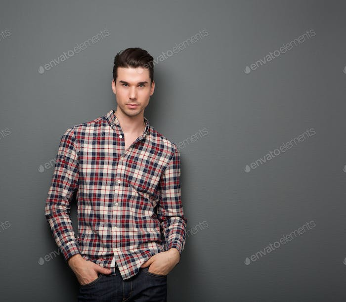 Relaxed young man with checkered shirt posing