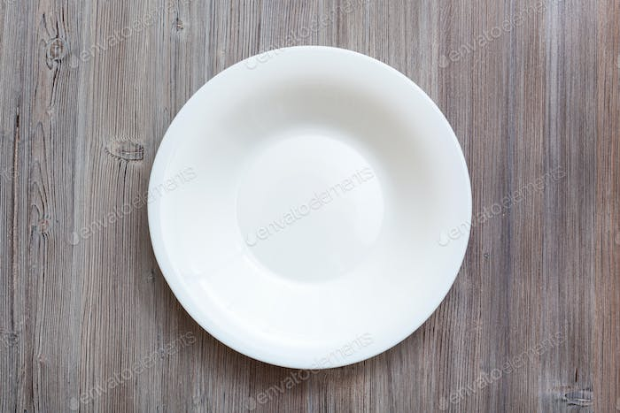 above view of white deep plate on gray brown table