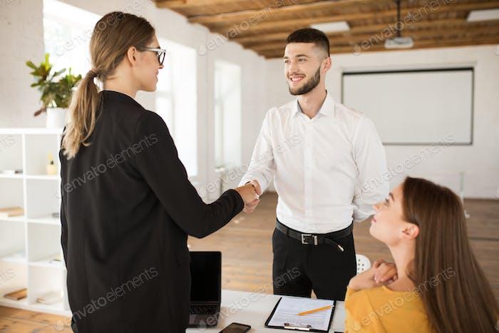 Радостный мужчина заявитель счастливо пожимает работодателю руку. Молодые руки