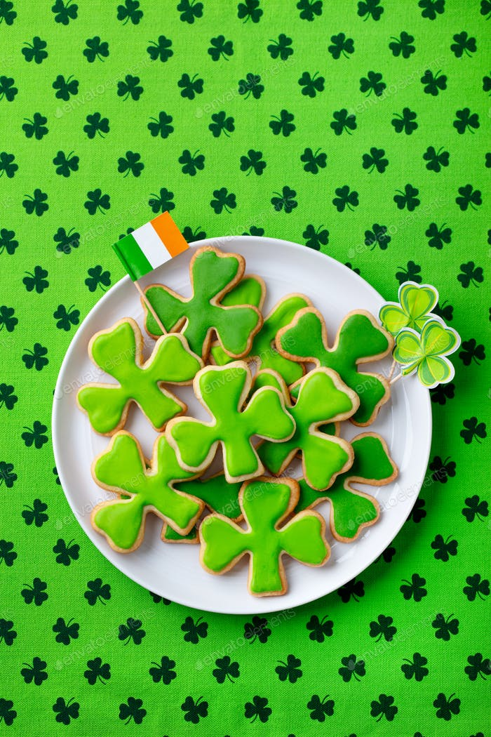 Shamrock cookies with Irish flag, St. Patrick's Day dessert. Green textile background. Top view