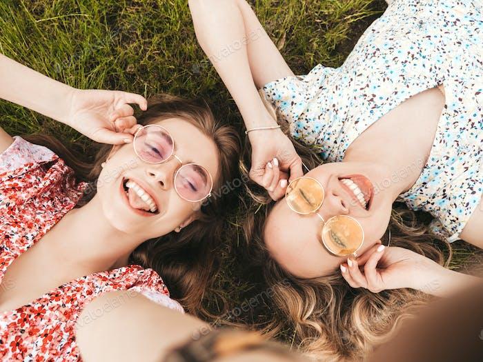 Portrait of two young cute women posing outdoors