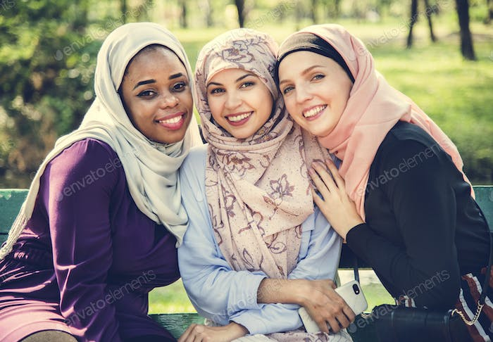 Islamic friends sitting at the park and smiling to camera