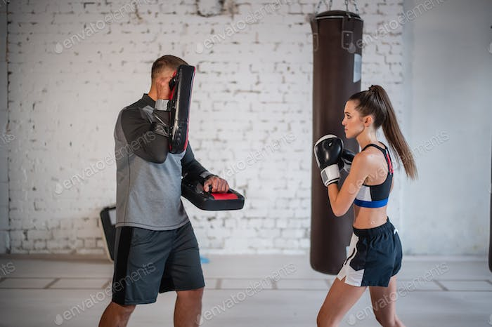 A young female athlete in good physical shape conducts kickboxing training under the supervision of