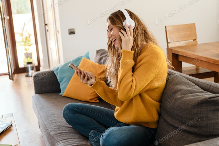 Joyful girl in headphones using cellphone while resting on couch