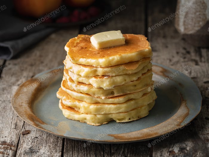 Pancake with butter, close-up. Dark moody old rustic wooden background.
