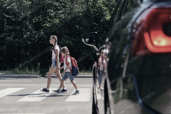 Low angle on car in front of children with backpacks walking thr