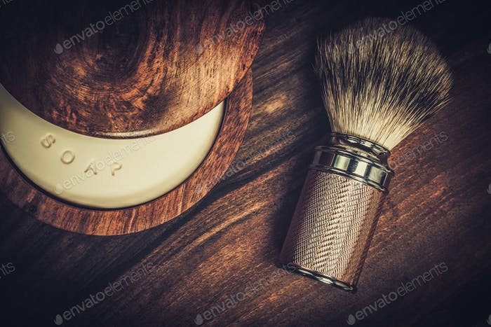 Shaving brush and soap on a luxury wooden background