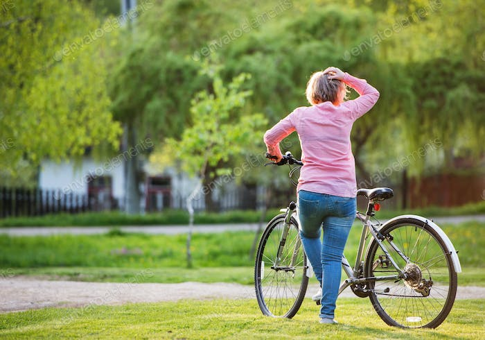 Senior woman with bicycle outside in spring nature.