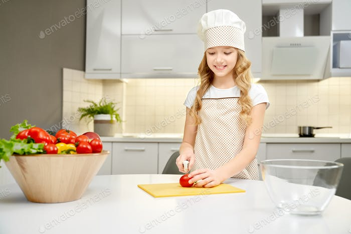 Cute girl in chef hat cutting vegetables on chopping board