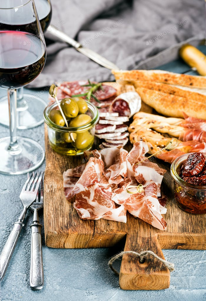 Meat appetizer selection. Salami, prosciutto, bread sticks, baguette, olives and sun-dried tomatoes