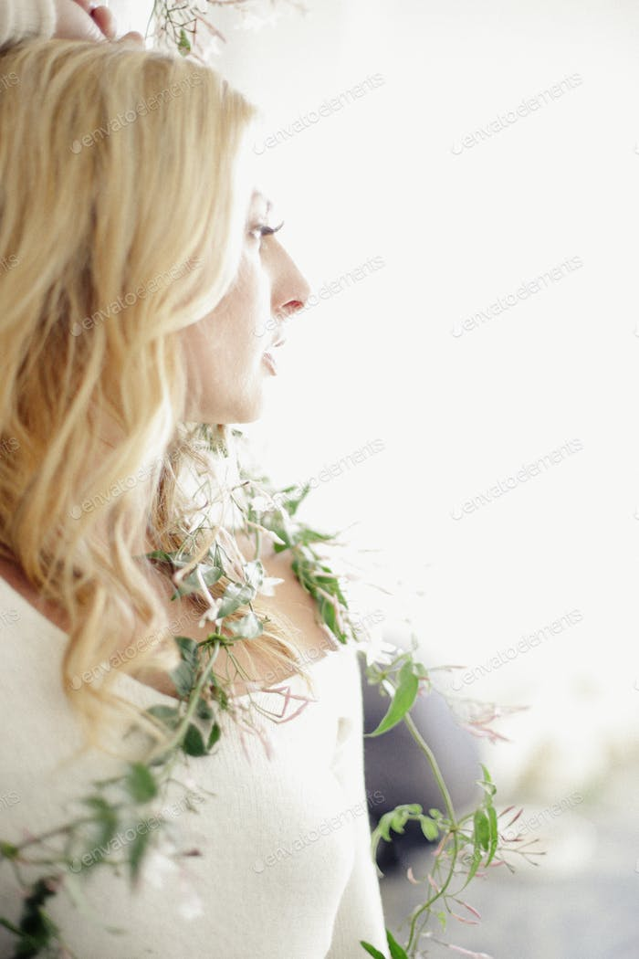 Head and shoulders portrait of a blonde woman, a creeper plant wrapped around her body.