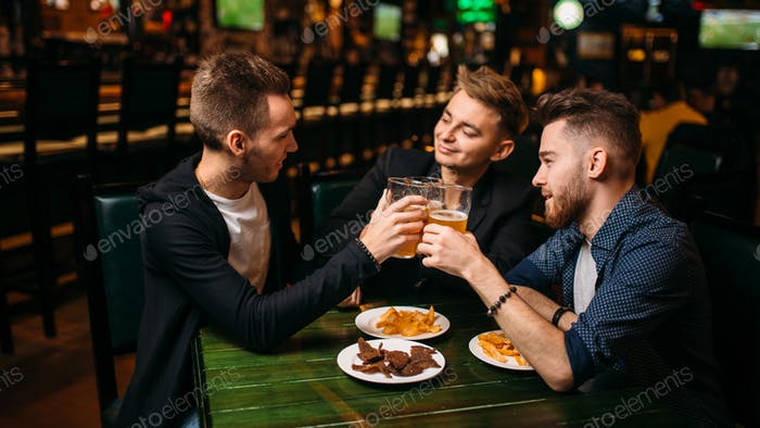 Men raised their glasses with beer in sport pub