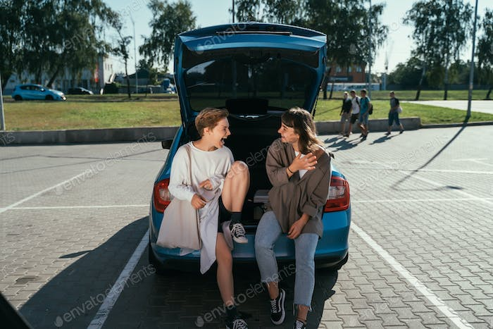 Two girls in the parking lot at the open trunk posing for the camera