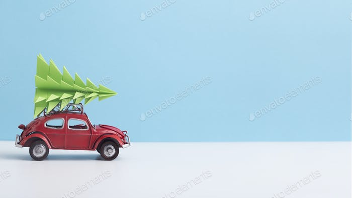 Red toy car with pine tree on the top on background
