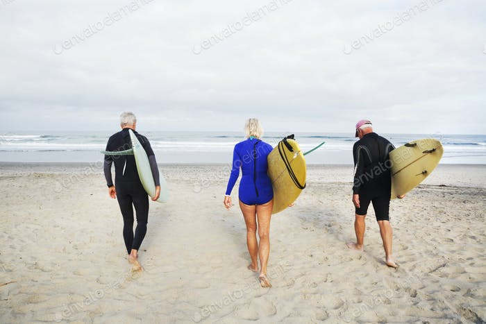 Senior woman and two senior men on a beach, wearing wetsuits and carrying surfboards.