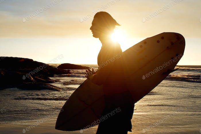 Young man carrying a surfboard at sunset