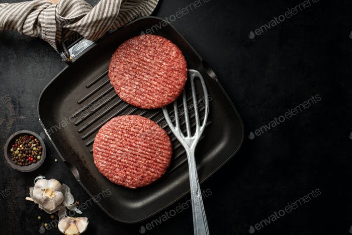 Raw burger meat on board