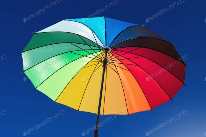 Umbrella rainbow colors on blue sky background