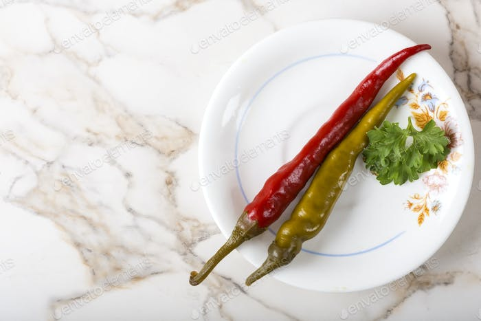 Pickled green and red pepperoni pepper on plate