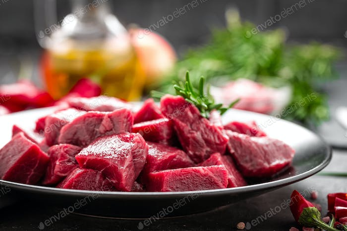 Raw beef meat sliced on black background