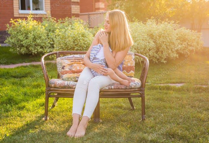 Porträt von glücklich liebevolle Mutter und ihr Baby im Freien.