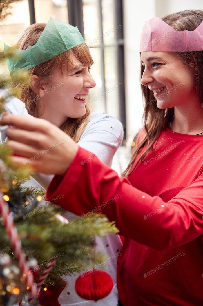 Gay weibliches Paar zu Hause Hängende Dekorationen auf Weihnachtsbaum zusammen
