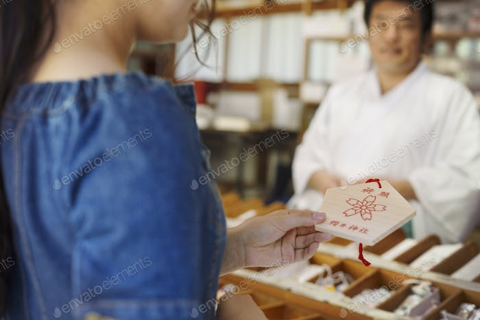 Young woman wearing blue dress buying wooden fortune telling plaque at Shinto Sakurai Shrine,