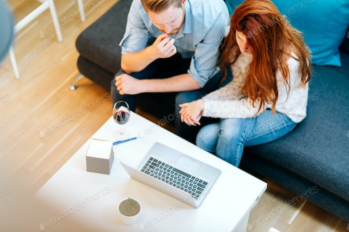 Couple browsing web together in living room