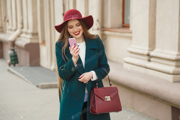 Beautiful stylishly dressed young woman receives a phone call