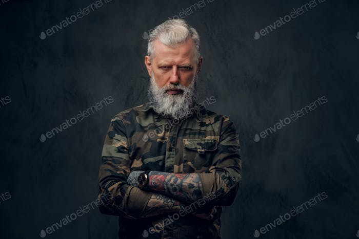 Military grandfather in camouflage clothing poses in dark background