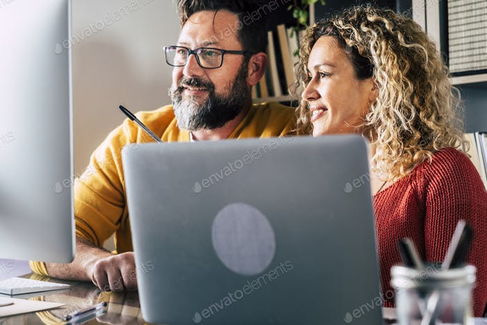 People at work at home with internet connection and computer laptop in couple