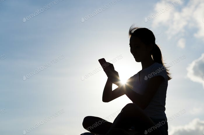 Silhouette of woman using cellphone under skyline in the evening