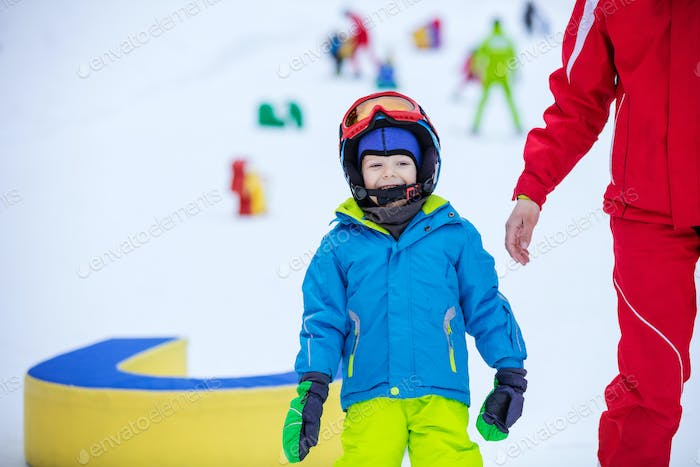 Happy young boy standing beside instructor in children's area