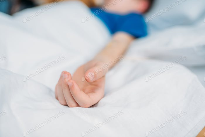 partial view of little boy lying in hospital bed