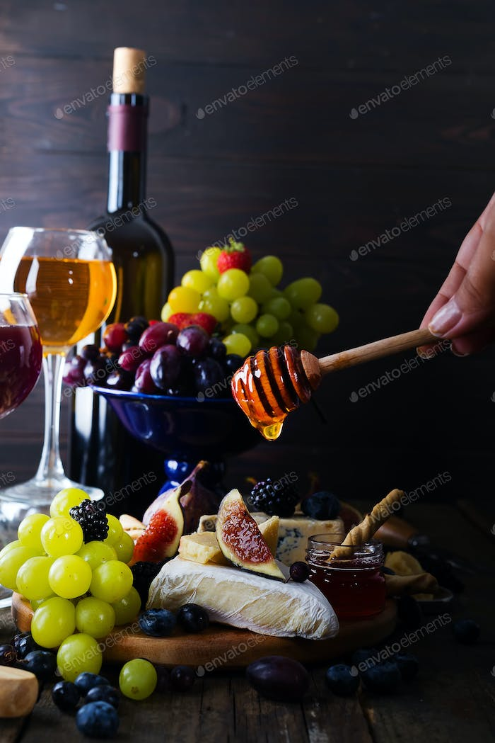 Cheese plate served with wine, jam and in his hand a stick with honey