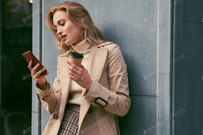 Attractive casual blond girl in trench coat with coffee to go dreamily using cellphone outdoor