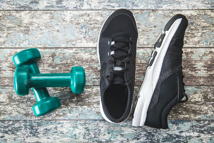 Black sport shoes and green dumbbells.